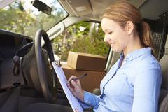 Female Delivery Driver Sitting In Van Filling Out Paperwork - stock photo