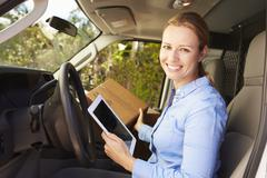 Female Delivery Driver Sitting In Van Using Digital Tablet - stock photo
