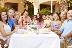 Large Family Group Enjoying Meal On Terrace Together - stock photo