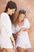 Female Friends On Holiday Together Using Mobile Phone Stock Photos