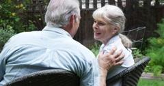 Sweet senior couple talking in their yard Stock Footage