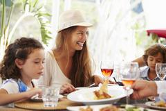 Mother With Children Enjoying Meal In Restaurant Stock Photos