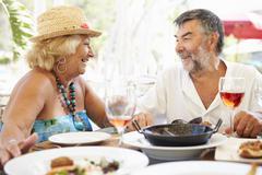 Senior Couple Enjoying Meal In Outdoor Restaurant Stock Photos