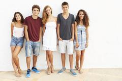 Portrait Of Teenage Group Leaning Against Wall - stock photo