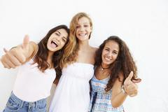 Portrait Of Three Teenage Girls Leaning Against Wall Stock Photos