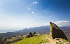 Man on the cliff in mountains at above sea Stock Photos
