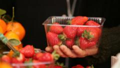 Fruiterer putting strawberries in plastic basket at fruit and vegetable shop Stock Footage