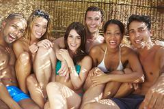 Group Of Friends In Swimwear Relaxing Outdoors Together Stock Photos
