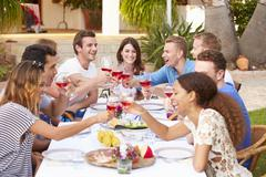 Large Group Of Young Friends Enjoying Outdoor Meal Together Stock Photos