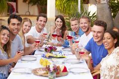 Large Group Of Young Friends Enjoying Outdoor Meal Together - stock photo