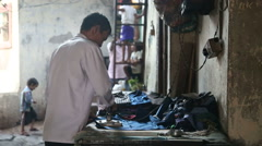 Men ironing clothes while a woman passes by. Stock Footage