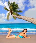Brunette tourist lying in beach sand tanning happy Stock Photos