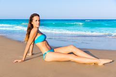 Brunette tourist sitting in beach sand tanning happy - stock photo