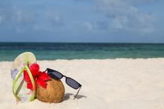 Coconut, hibiscus flower, sunglasses and flip flops on the beach Stock Photos