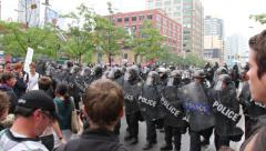 Stock Video Footage of 1080p 24fps - Police officers in line block demonstrators at busy corner