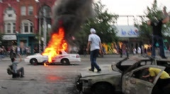 Stock Video Footage of 1080p 24fps - Rioters jump and set police cars on fire - HD 1080p