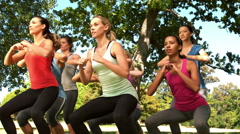 Fitness group squatting in park Stock Footage