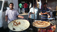 Men preparing and selling local food at a street stand in Mumbai. Stock Footage