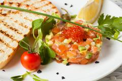 Stock Photo of Salmon Tartar on a light background. Starter close up