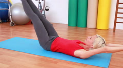 Blonde woman working on exercise mat Stock Footage