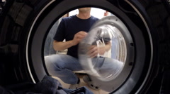 Washing machine inside. Man laying on linen washing Stock Footage