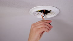 Installing a smoke detector to a ceiling outlet 4K Stock Footage