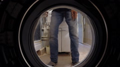 Washing machine inside. Man laying on linen washing - stock footage