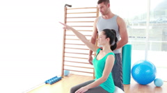 Stock Video Footage of Trainer assisting woman exercising on fitness ball