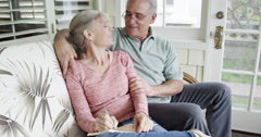 Happy senior couple sitting and writing in journal Stock Footage