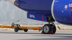 Ground crew member removing  wheel chocks from Boeing 737 tires at International Stock Footage