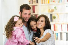 Cute family with two little girls taking a selfie photo - stock photo