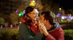 Young couple cuddling on date in night city. Attractive girl sitting on his lap Stock Footage