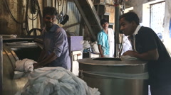 Indian men in laundry manufactory in slum of Mumbai. - stock footage