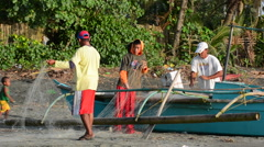 People cleaning there fishing net on the beach in Philippines Stock Footage