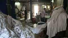 Men working in a laundry manufactory surrounded by piles of laundry. - stock footage