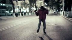 Funny guy walk down the night street city, free dancing to music in headphones Stock Footage