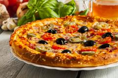 Pizza with bacon, olives and jalapeno pepper on a plate - stock photo