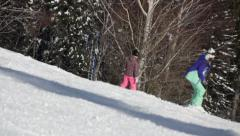Snowboarders ride on the slope in ski resort Stock Footage