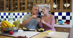 Senior couple using smartphone in kitchen Stock Footage