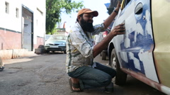 Indian men repainting a car on the street of Mumbai while people pass by. Stock Footage