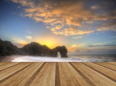 Beautiful sunrise over ocean with rock stack in foreground with wooden planks Stock Photos