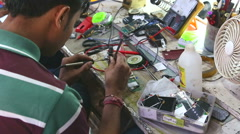 Man fixing electrical components with a specialized tool in workshop in Mumbai. Stock Footage