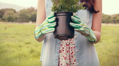 Happy woman holding potted flowers Stock Footage
