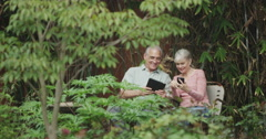 Happy senior couple using tablet smartphone outside in yard - stock footage