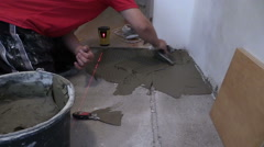 Man distribute mass tile glue on floor. Laser level measure Stock Footage