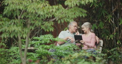Happy senior couple using tablet smartphone outdoors - stock footage
