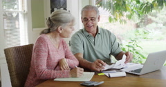 Senior couple paying bills together on laptop Stock Footage