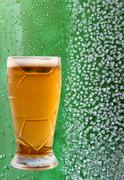 Beer glass on ice crystals and drips green background. - stock photo