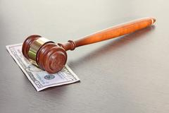 Judge gavel with fifty dollars banknote on wooden table. Stock Photos