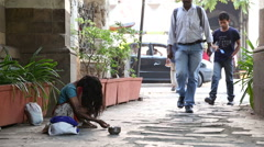 Young girl begging on the street of Mumbai while people pass by. Stock Footage